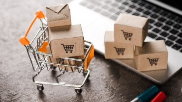 selective focus of toy shopping cart with small carton boxes near laptop, e-commerce concept